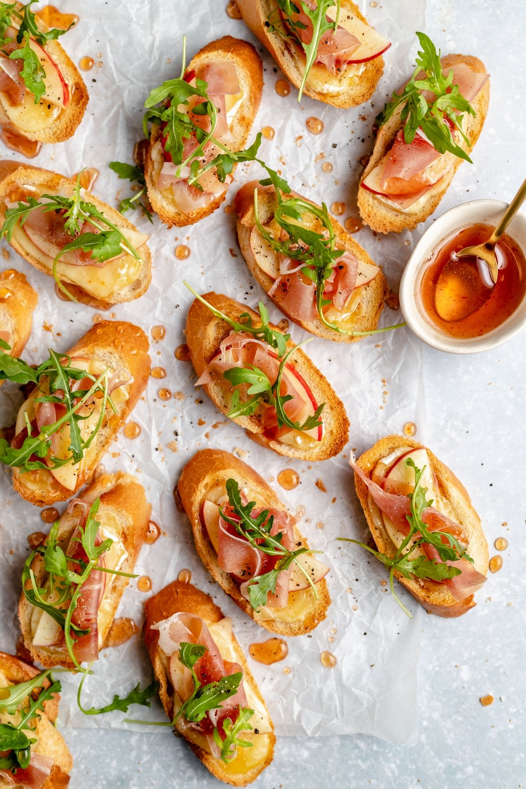 apple & brie crostini with hot honey on parchment paper