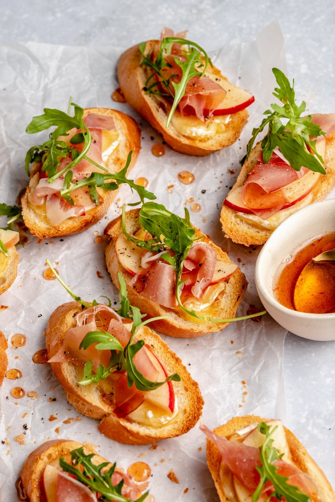 apple and brie crostini with prosciutto and arugula on parchment paper