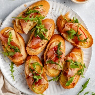 apple and brie crostini with prosciutto on a plate