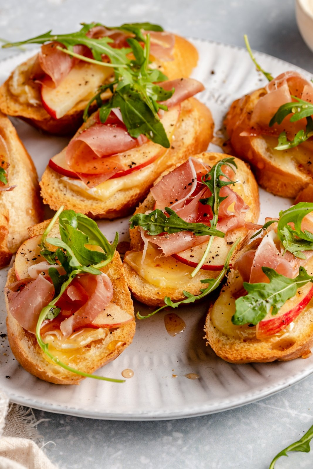 simple apple and brie crostini with prosciutto on a plate