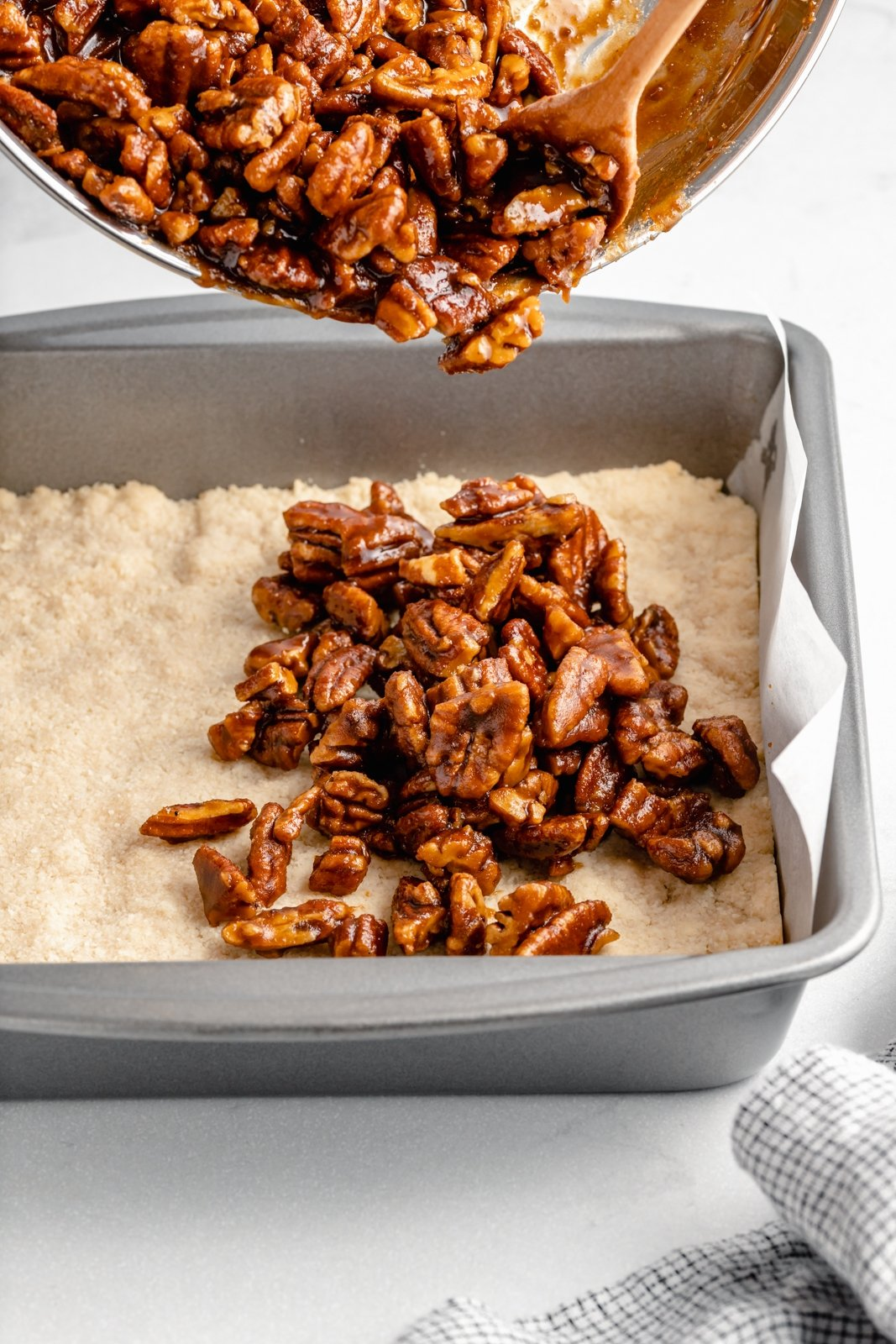 pouring healthy pecan pie bar filling into a baking dish