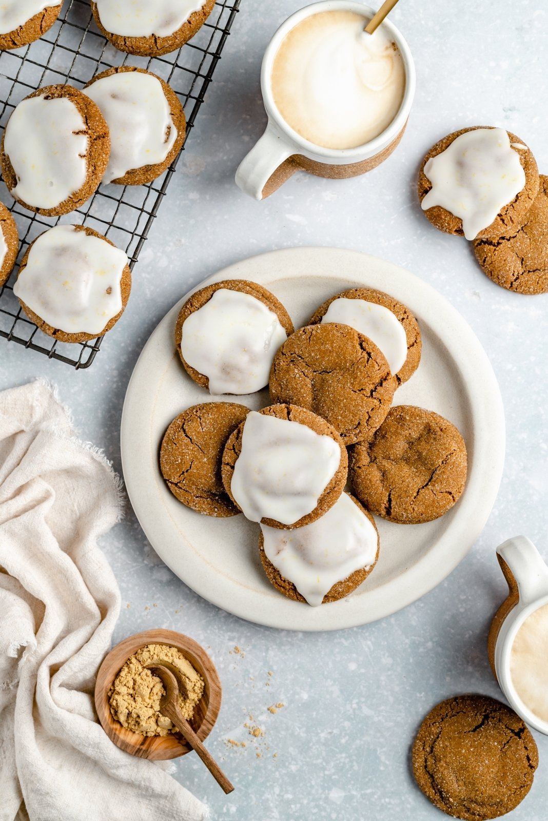 brown butter ginger cookies with icing on a plate and on a wire rack