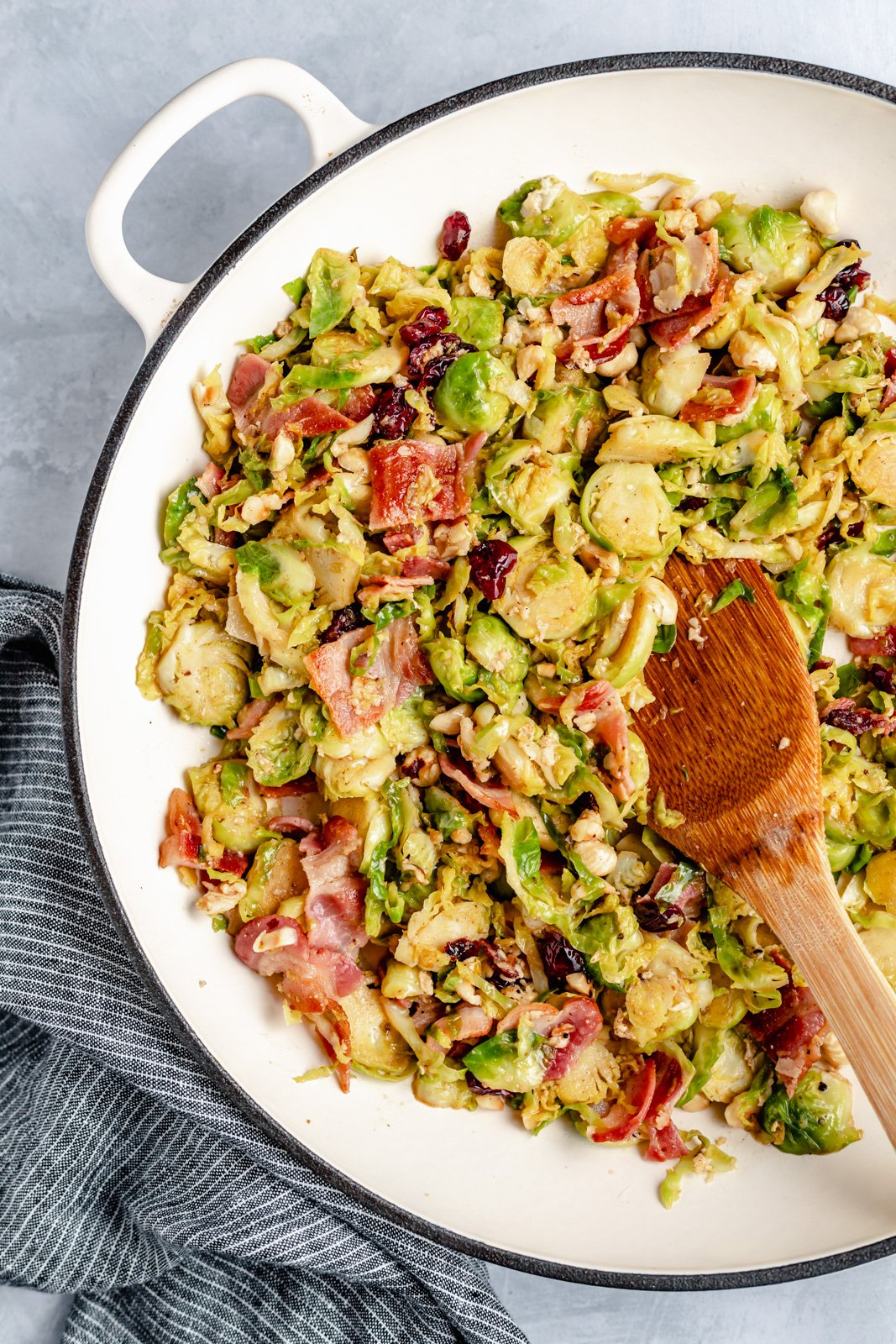 warm brussels salad in a skillet with a wooden spoon