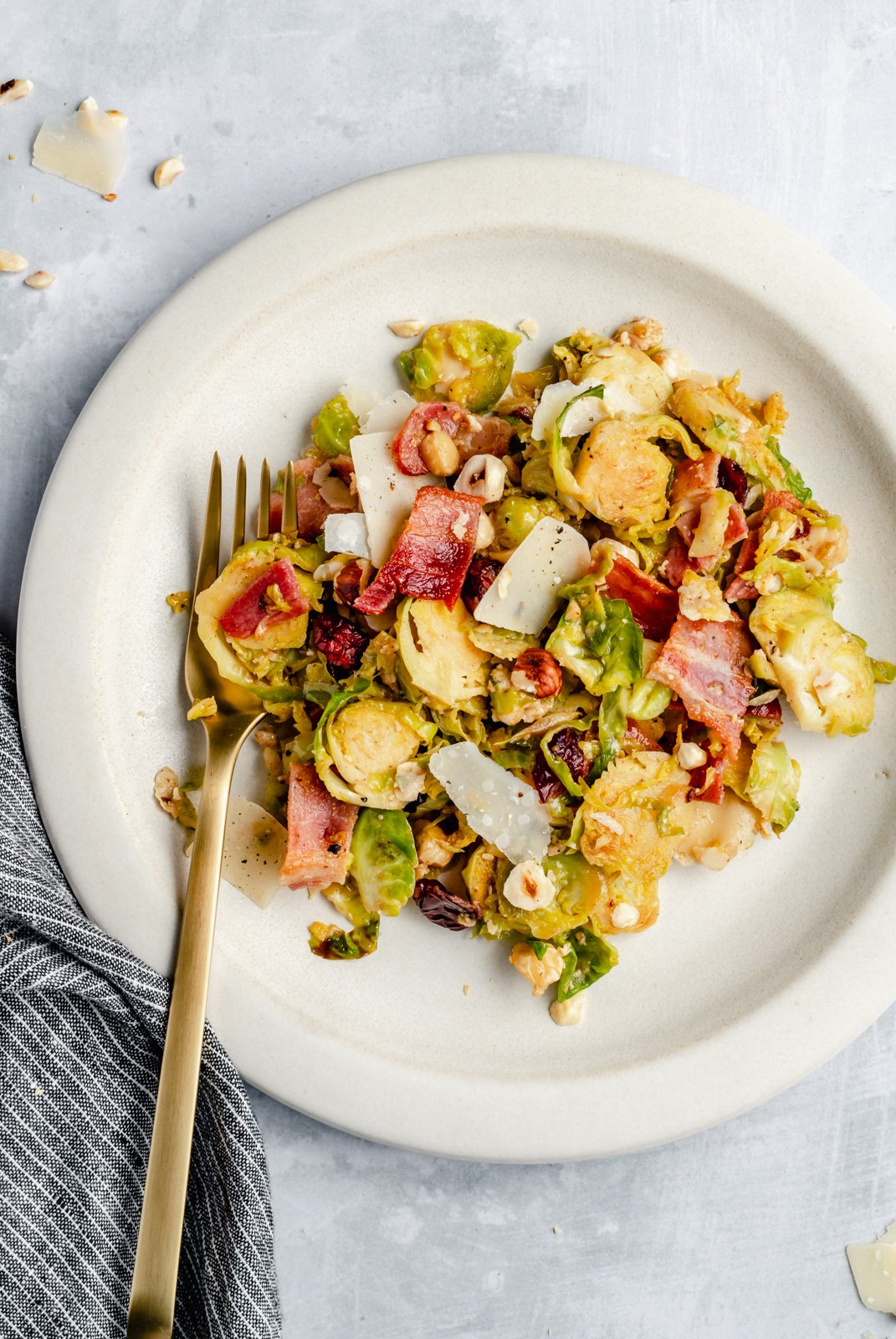 warm brussels sprouts salad with bacon on a plate with a fork