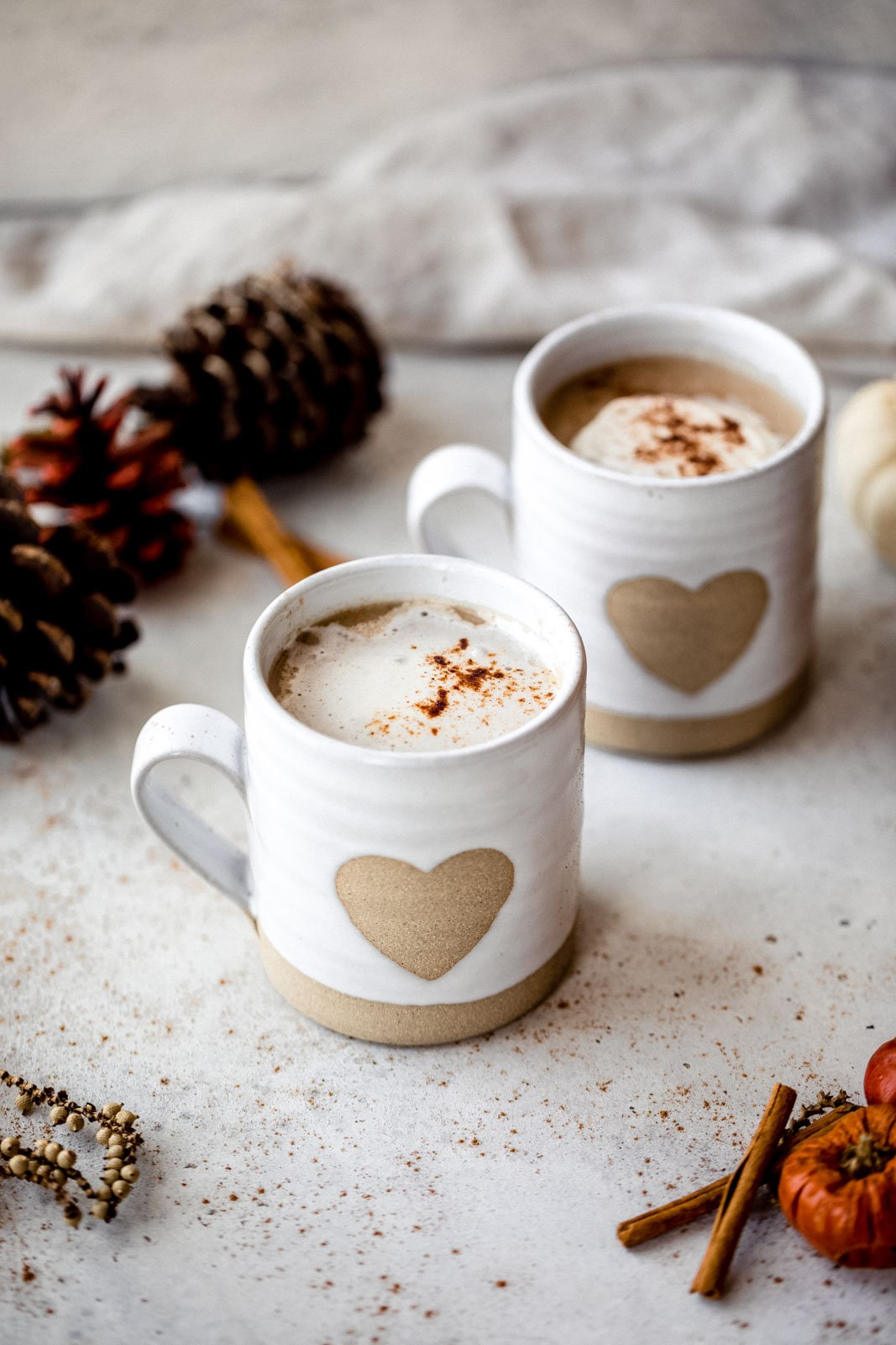 two chai ginger lattes in mugs next to pine cones