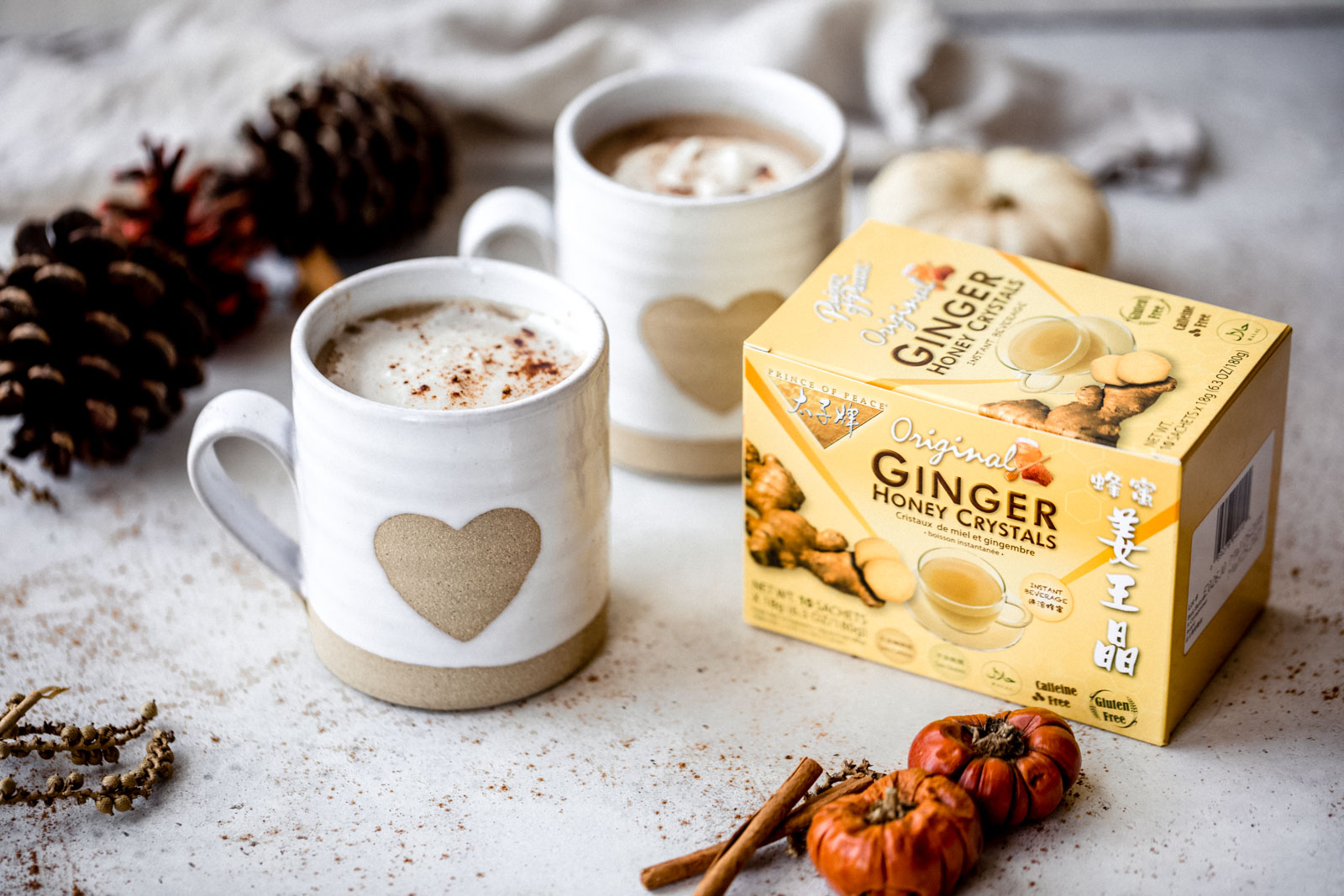 two ginger lattes next to a box of ginger honey crystals