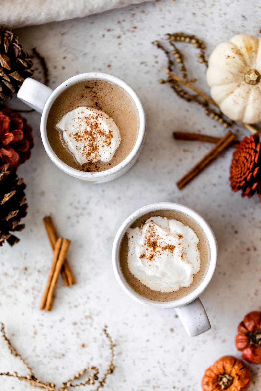 top-down view of two chai ginger lattes with whipped cream on top
