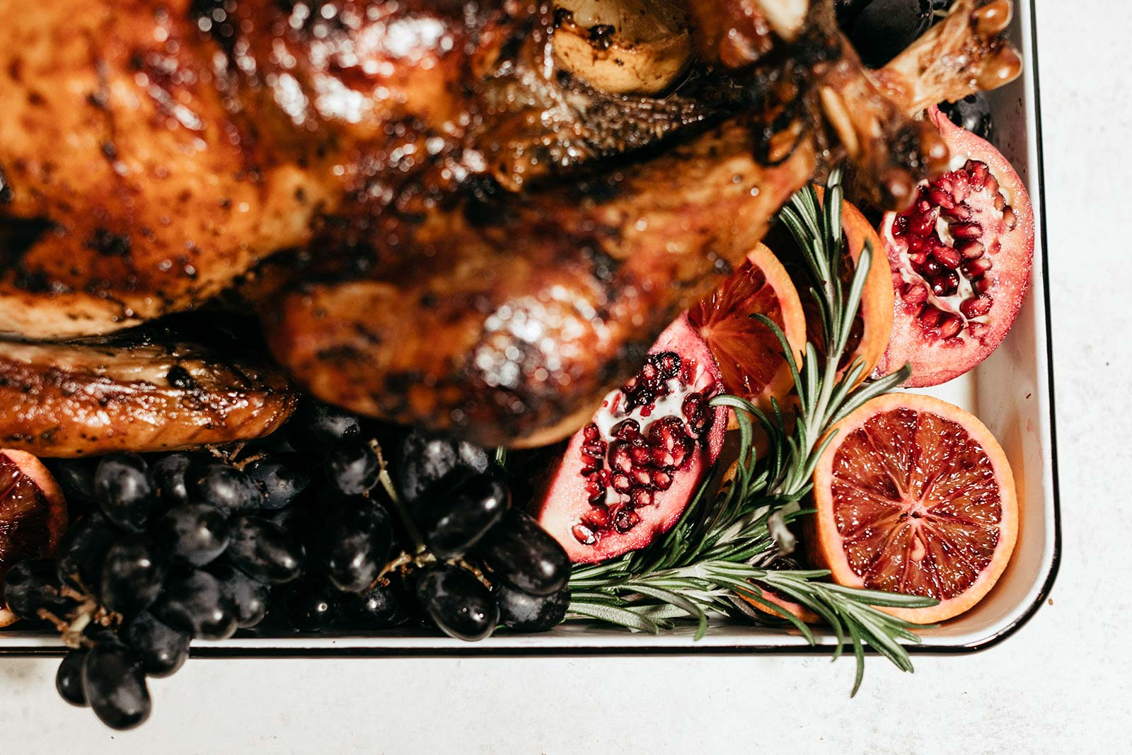 whole thanksgiving turkey on a platter with grapes and pomegranate