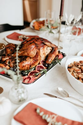 maple roasted turkey on a platter on a thanksgiving table