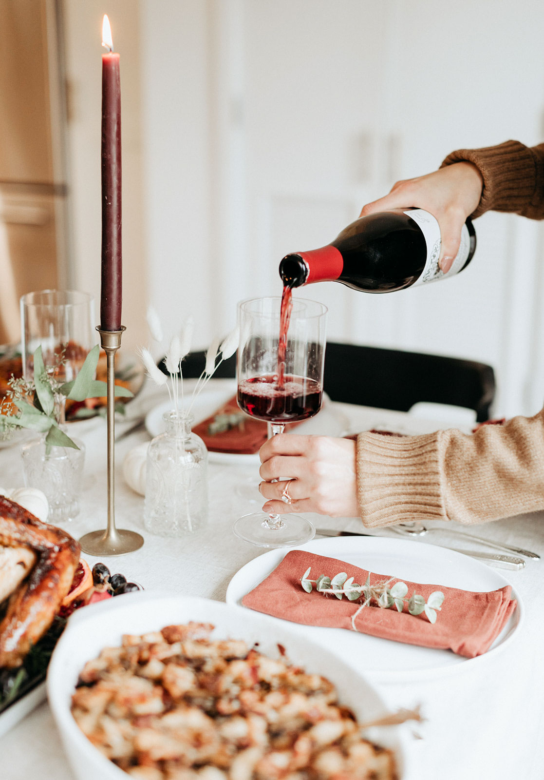 pouring wine into a glass on a thanksgiving table