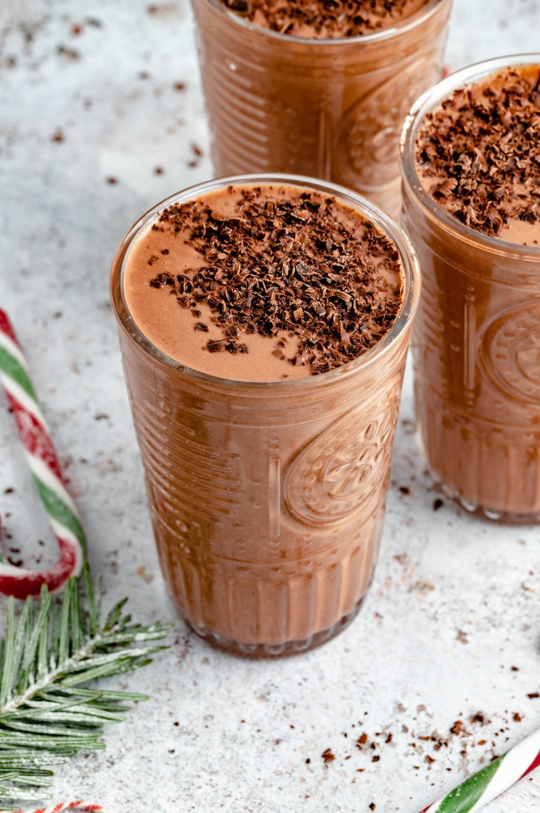 healthy mint chocolate smoothie in a glass topped with cacao nibs
