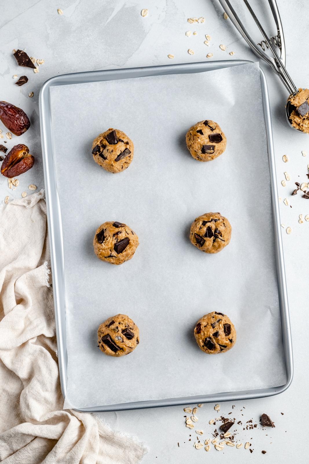 unbaked tahini date chocolate chunk oatmeal cookies on a baking sheet