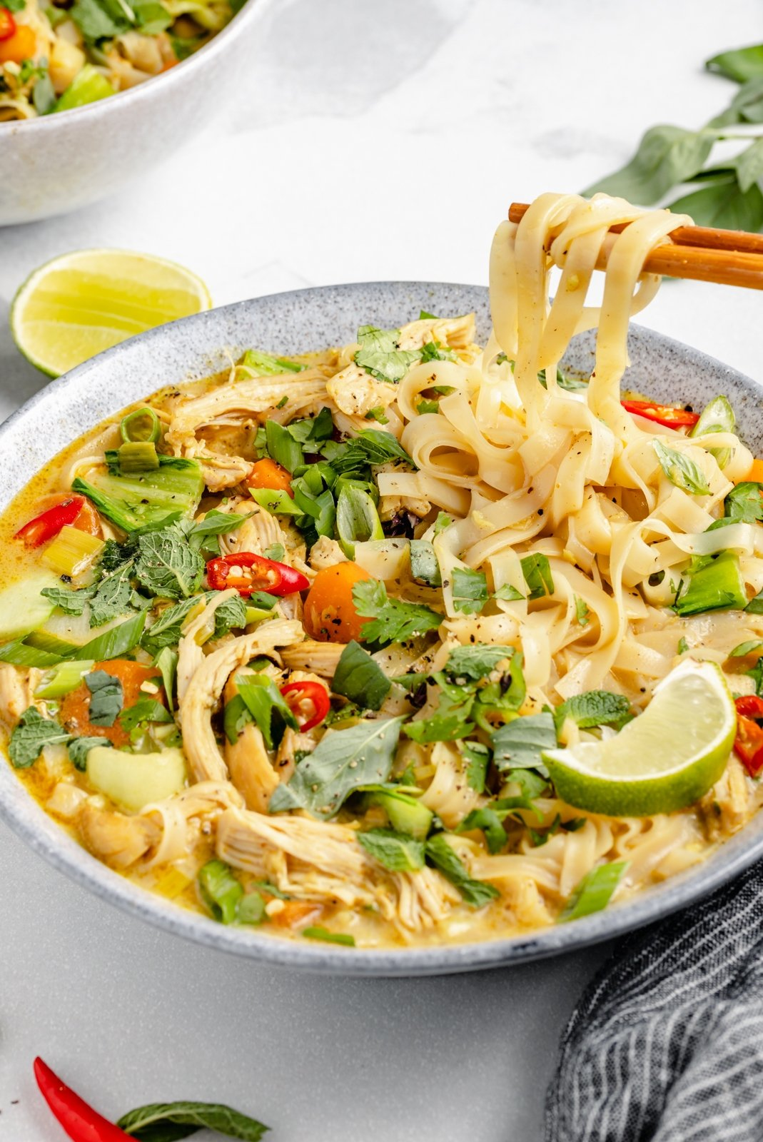 lifting noodles out of a bowl of curry chicken noodle soup