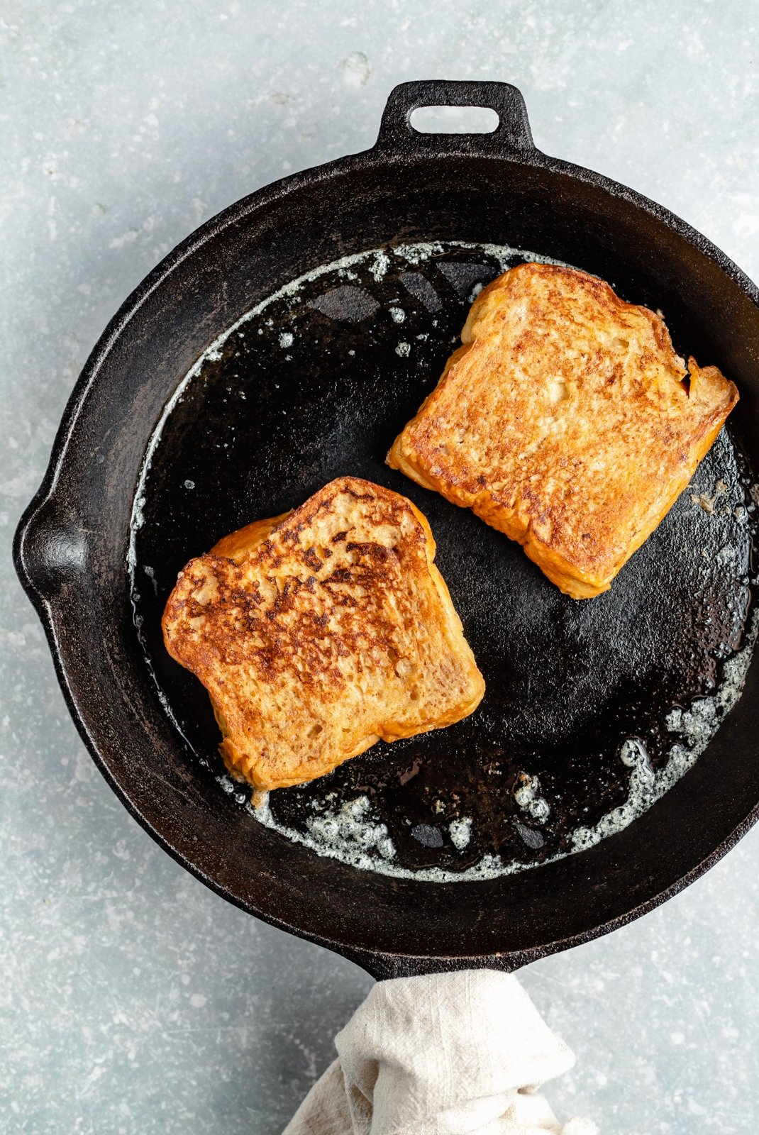 cooking two pieces of healthy french toast in a skillet