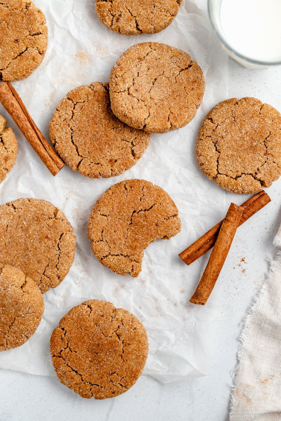 grain free snickerdoodles on parchment paper with cinnamon sticks