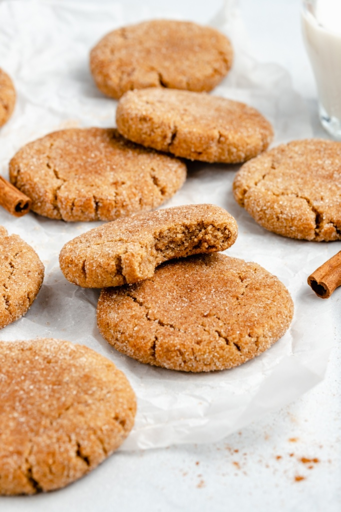 gluten free snickerdoodles on parchment paper with a bite taken out