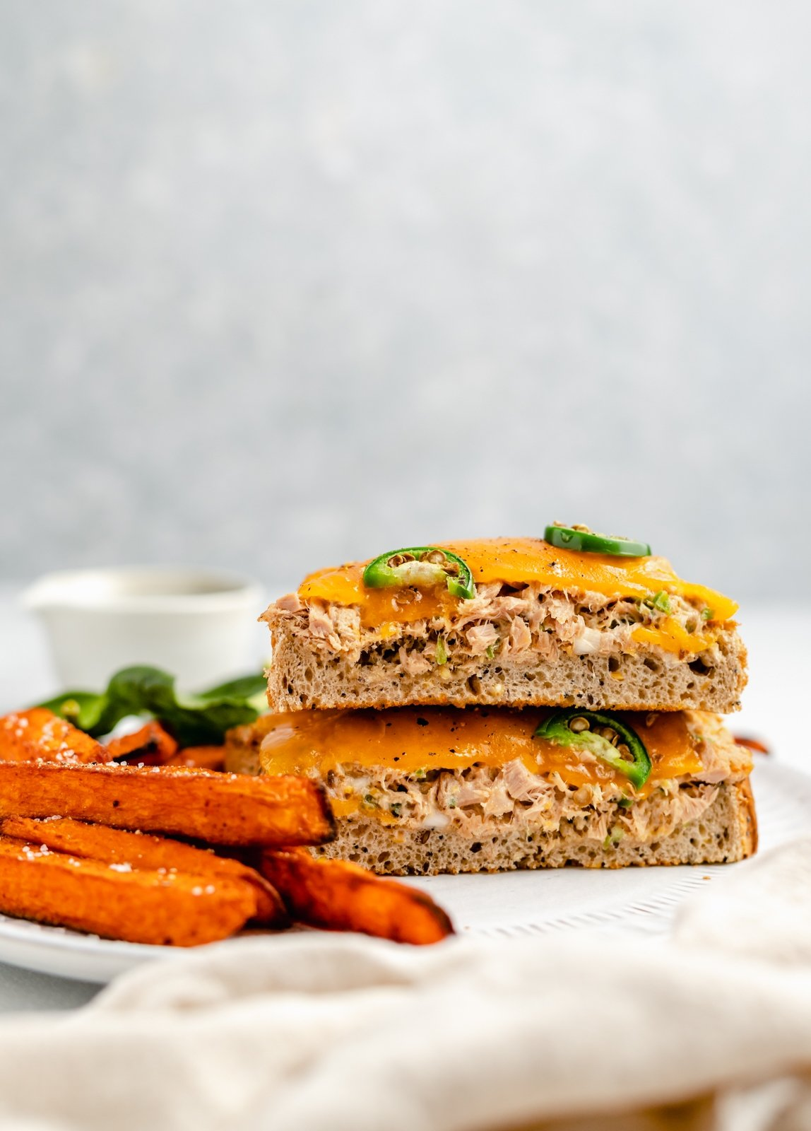 spicy tuna melt stacked on a plate with sweet potato fries