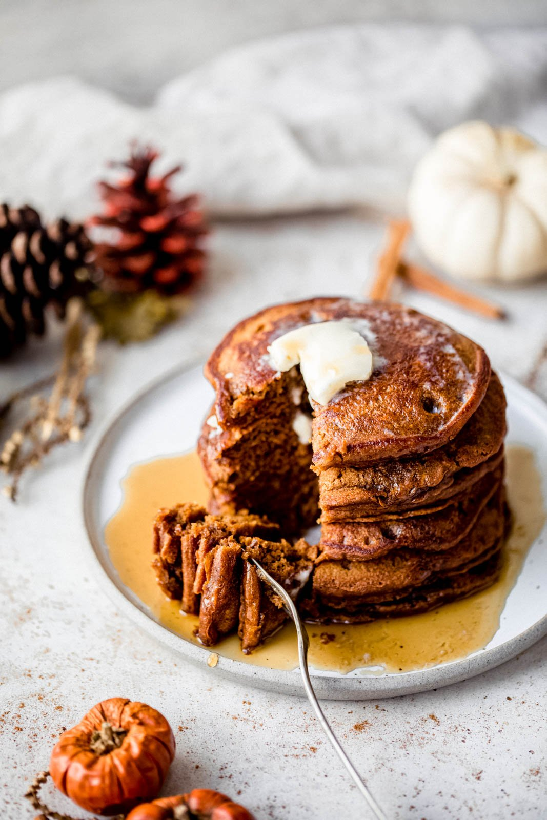 stack of gingerbread pancakes on a plate with a bite cut out