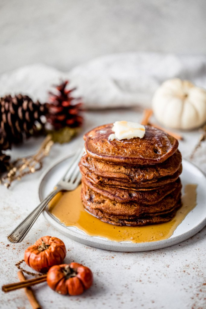 stack of gingerbread pancakes on a plate next to mini pumpkins
