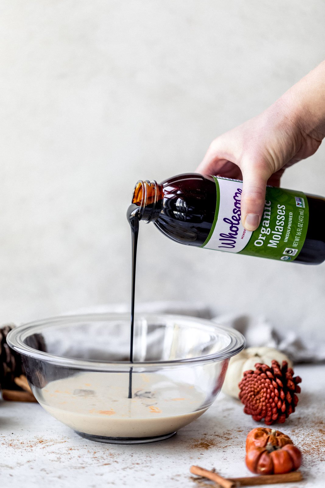 pouring molasses into a bowl for gingerbread pancakes