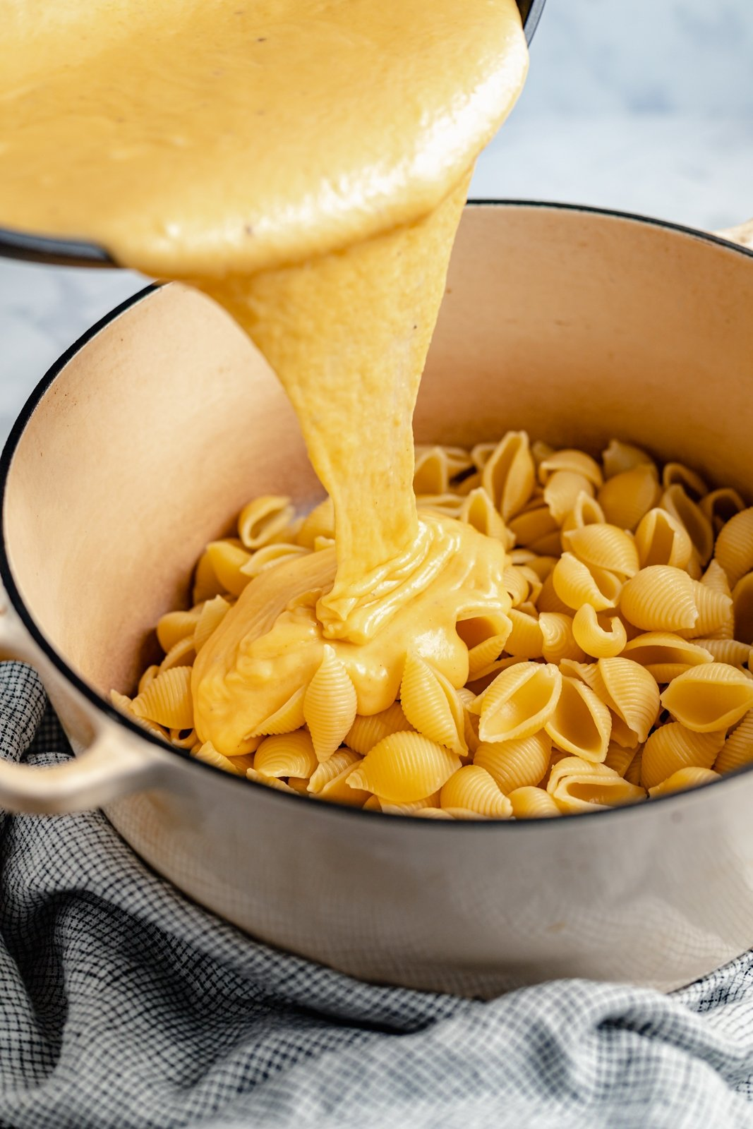 pouring cheese sauce onto buffalo mac and cheese