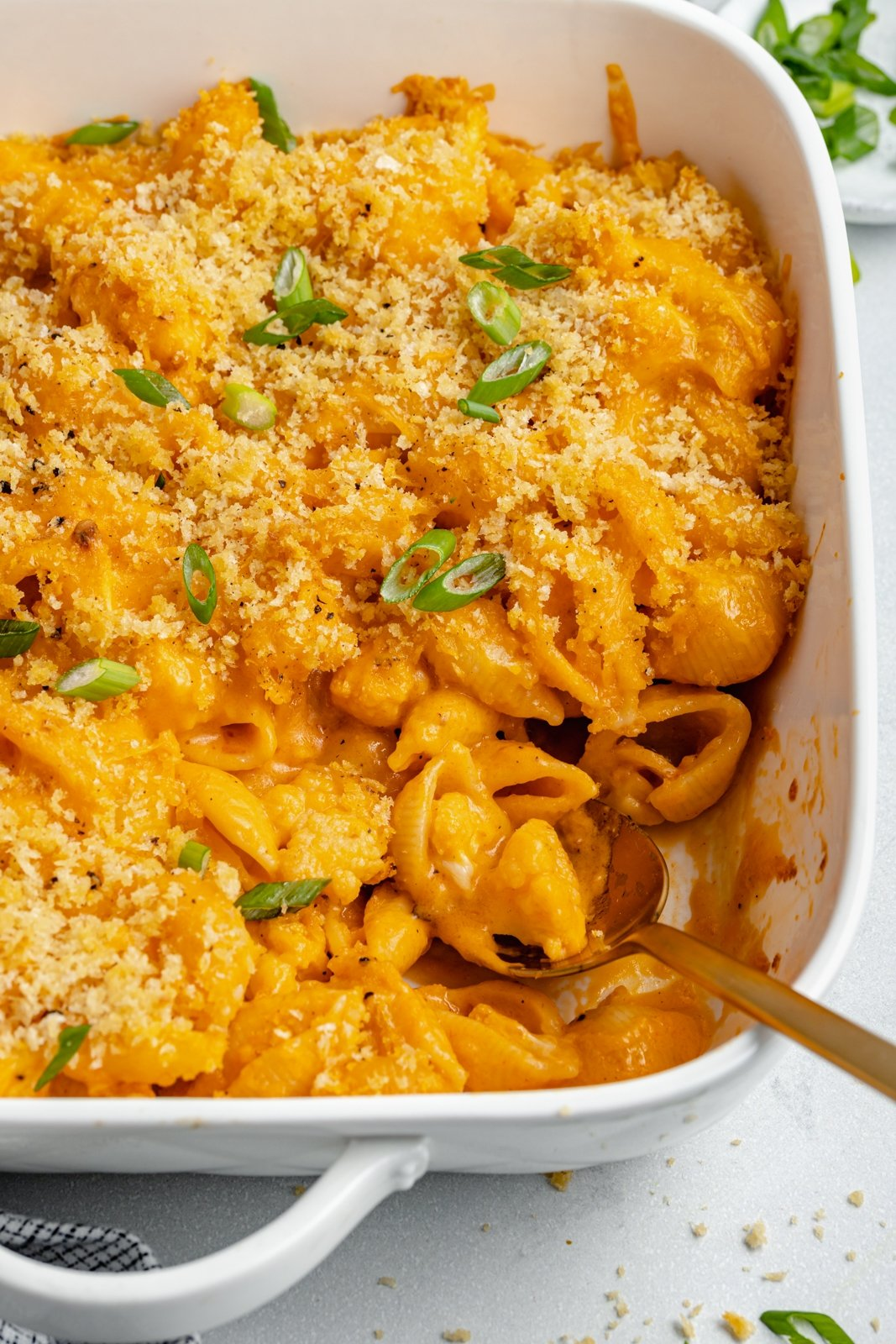buffalo cauliflower mac and cheese in a baking dish with a spoon