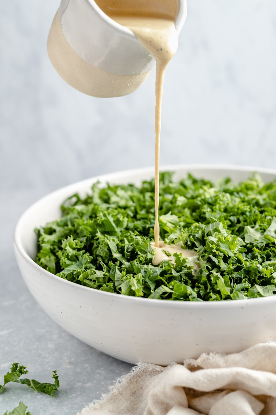 pouring tahini dressing onto a bowl of kale