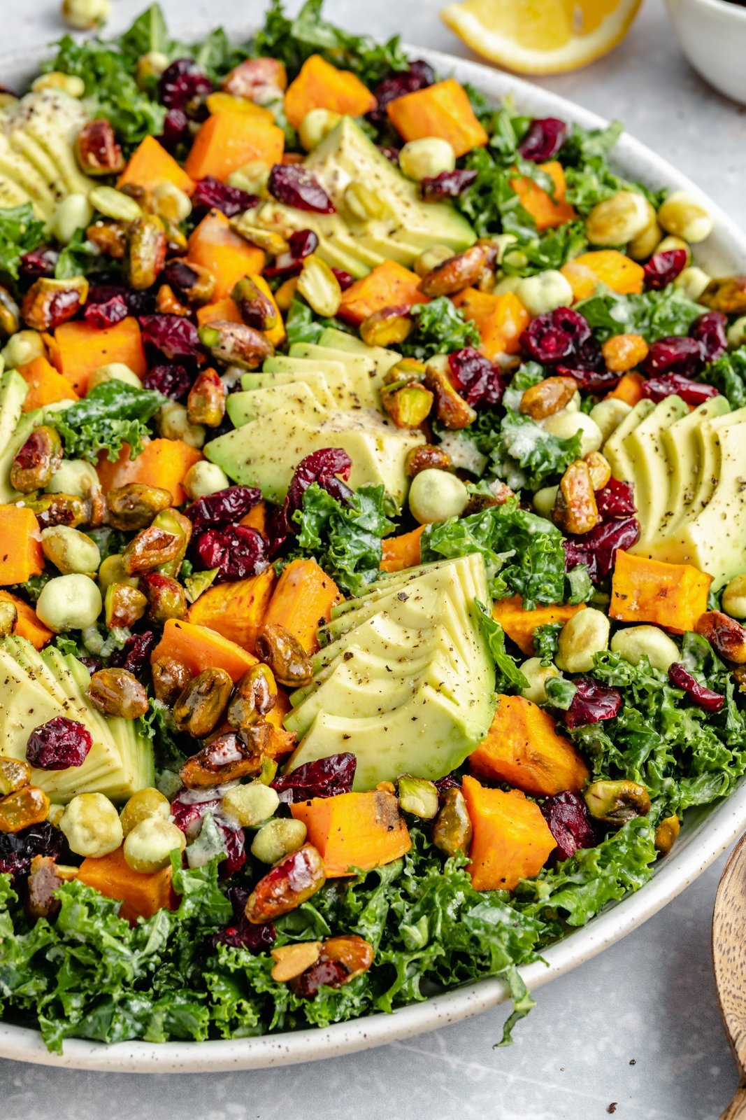 up-close shot of a kale and sweet potato salad with avocado and dried cranberries