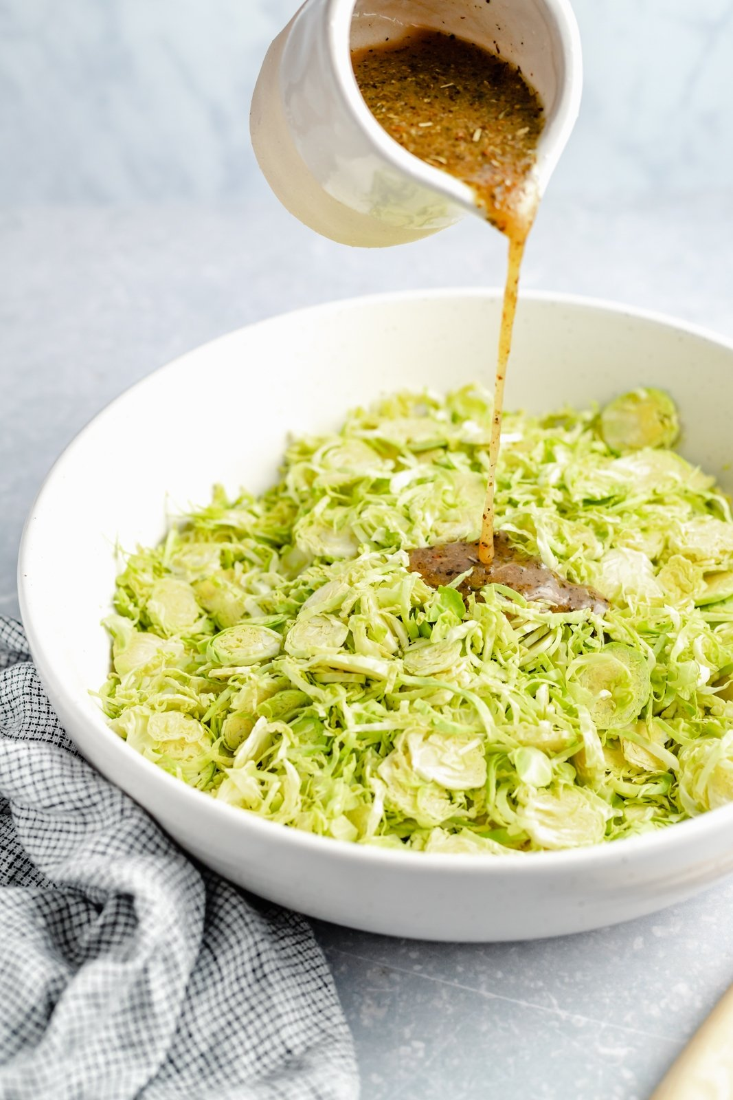 pouring italian dressing into a bowl of chopped brussels sprouts