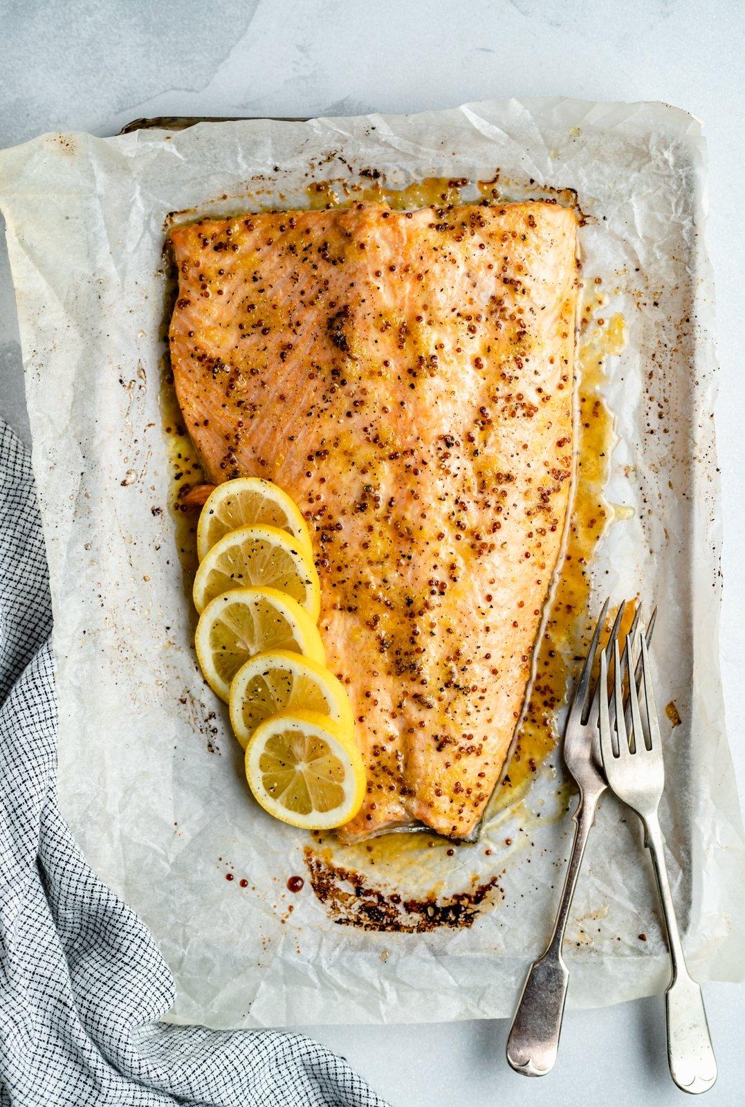 lemon garlic salmon on a baking sheet with lemon slices