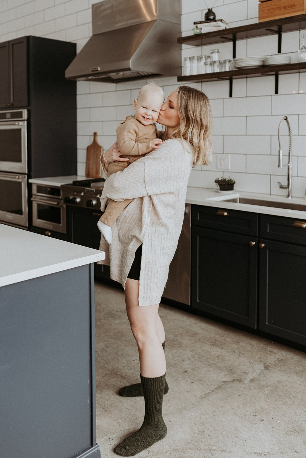 monique holding baby sidney in a kitchen