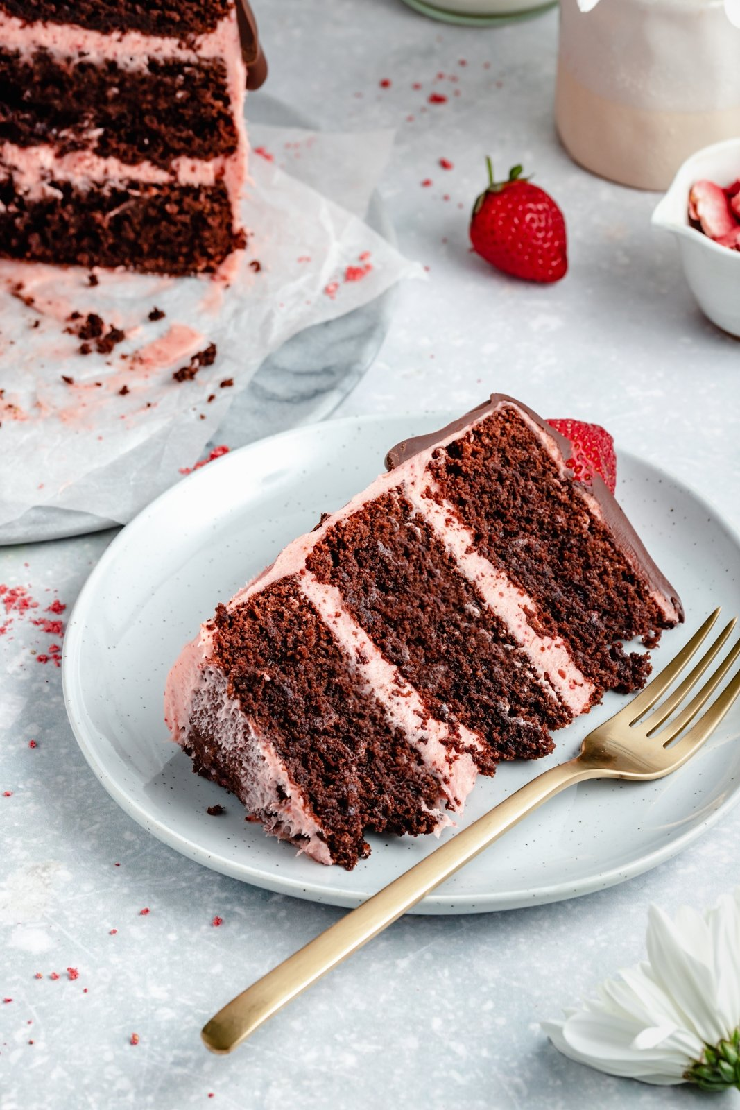 slice of healthy chocolate strawberry cake on a plate with a fork