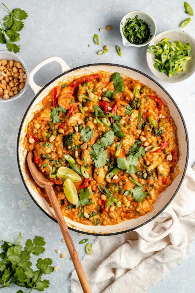 Thai peanut chicken couscous in a pan with a wooden spoon