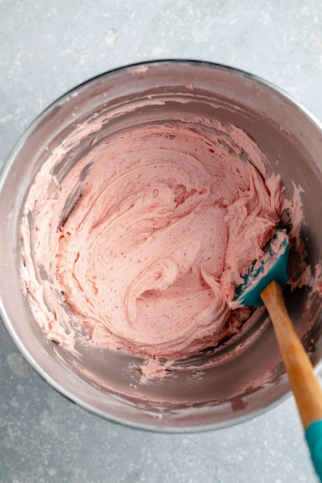 mixing strawberry buttercream frosting in a bowl
