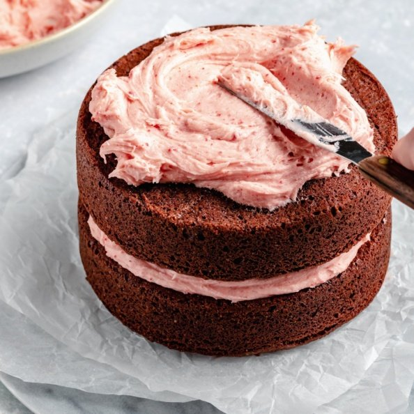 frosting a cake with strawberry buttercream frosting