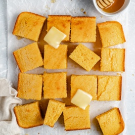 fluffy homemade cornbread cut into slices and topped with butter