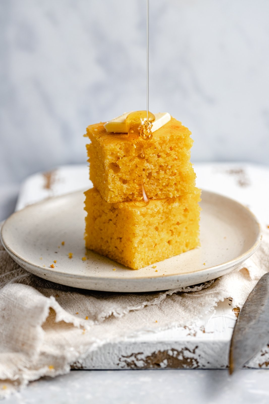 two slices of cornbread stacked, topped with butter and drizzled with honey