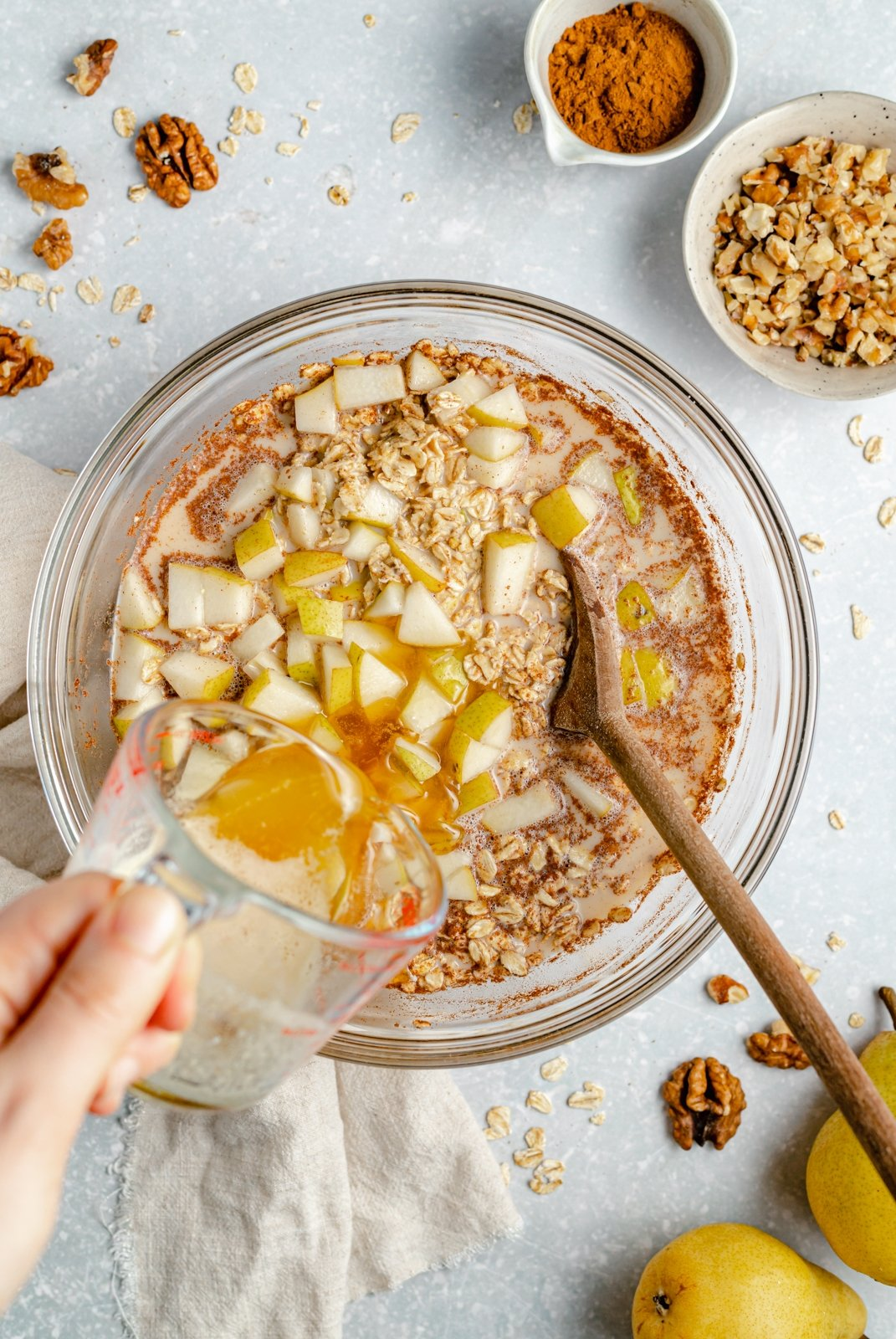 adding brown butter to a bowl with pear oatmeal bake ingredients