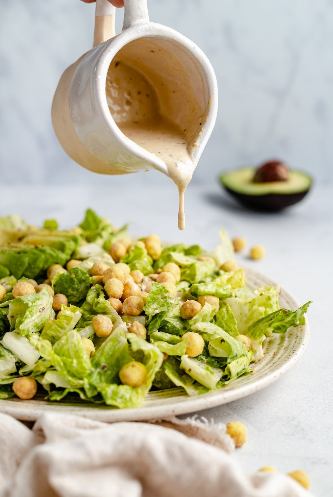 pouring dressing on a vegan caesar salad