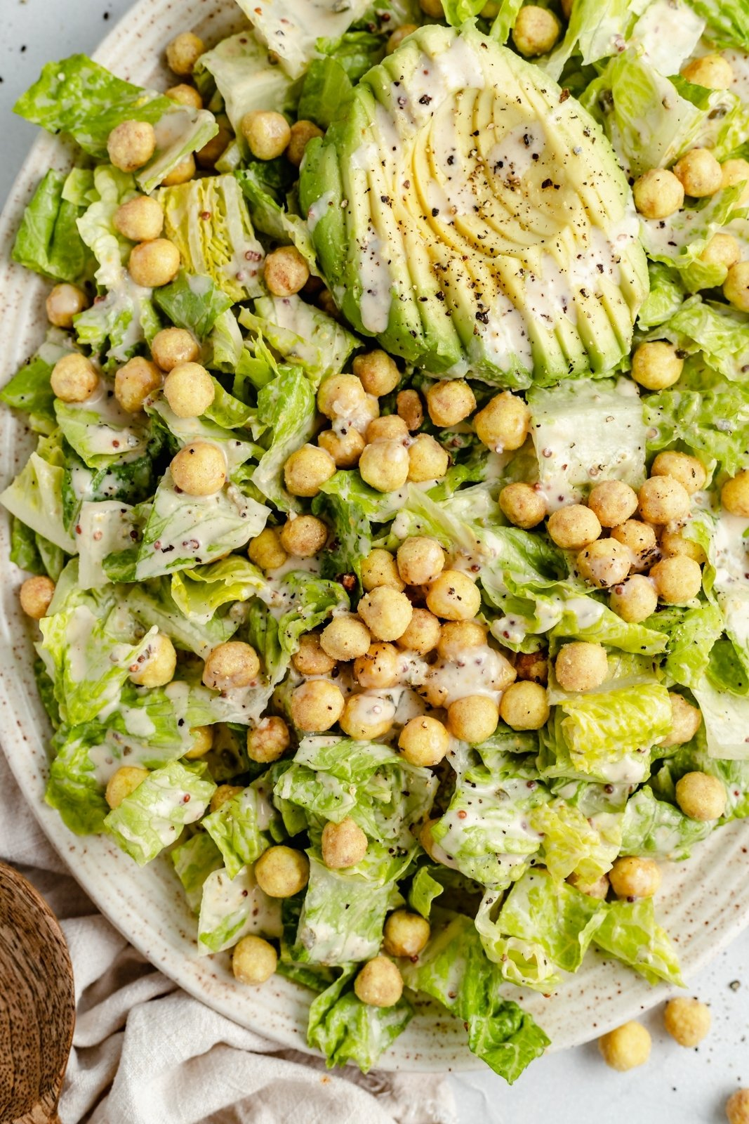 vegan caesar salad with chickpeas and avocado on a platter