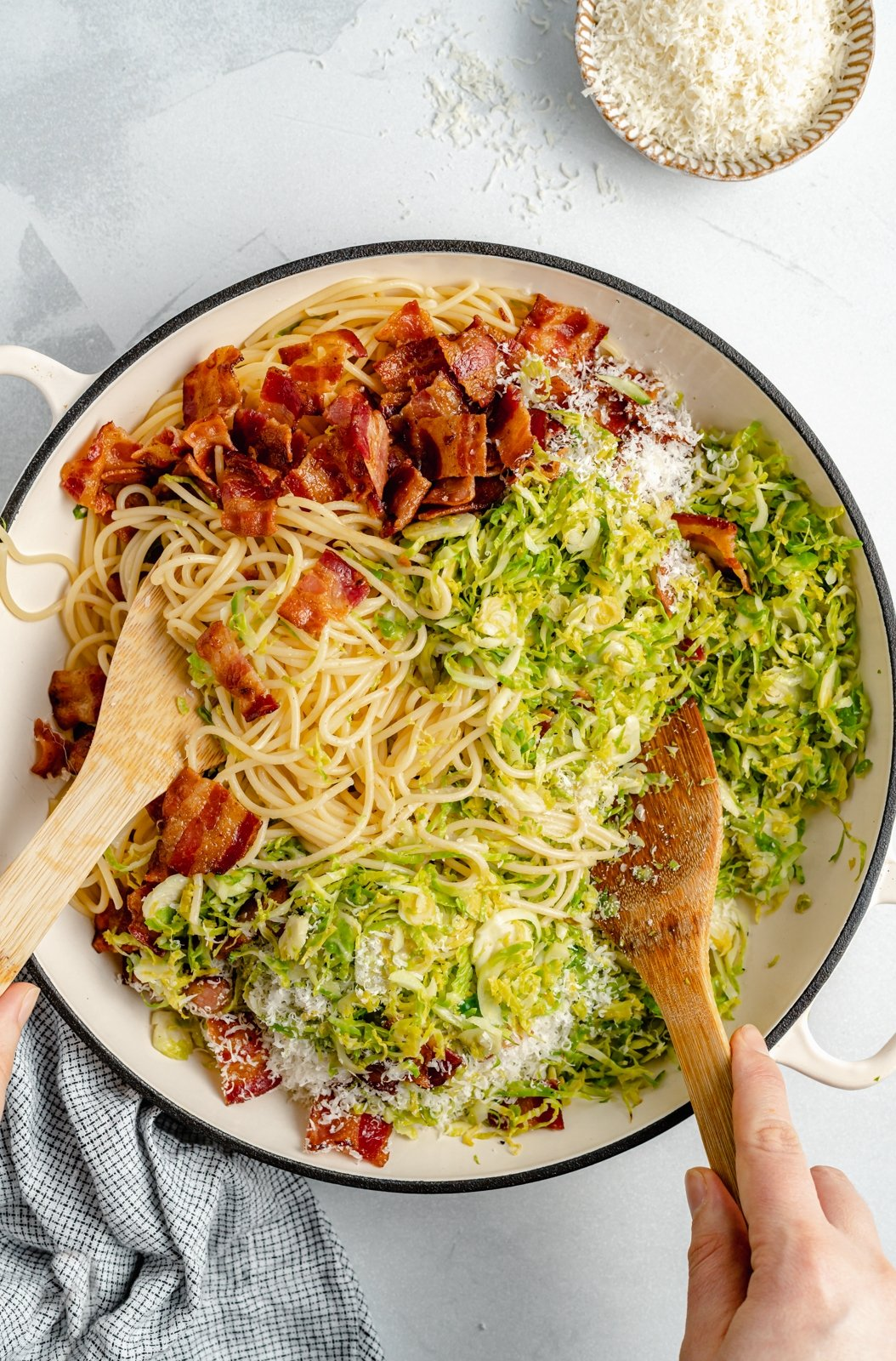 tossing brussel sprout spaghetti with bacon in a bowl