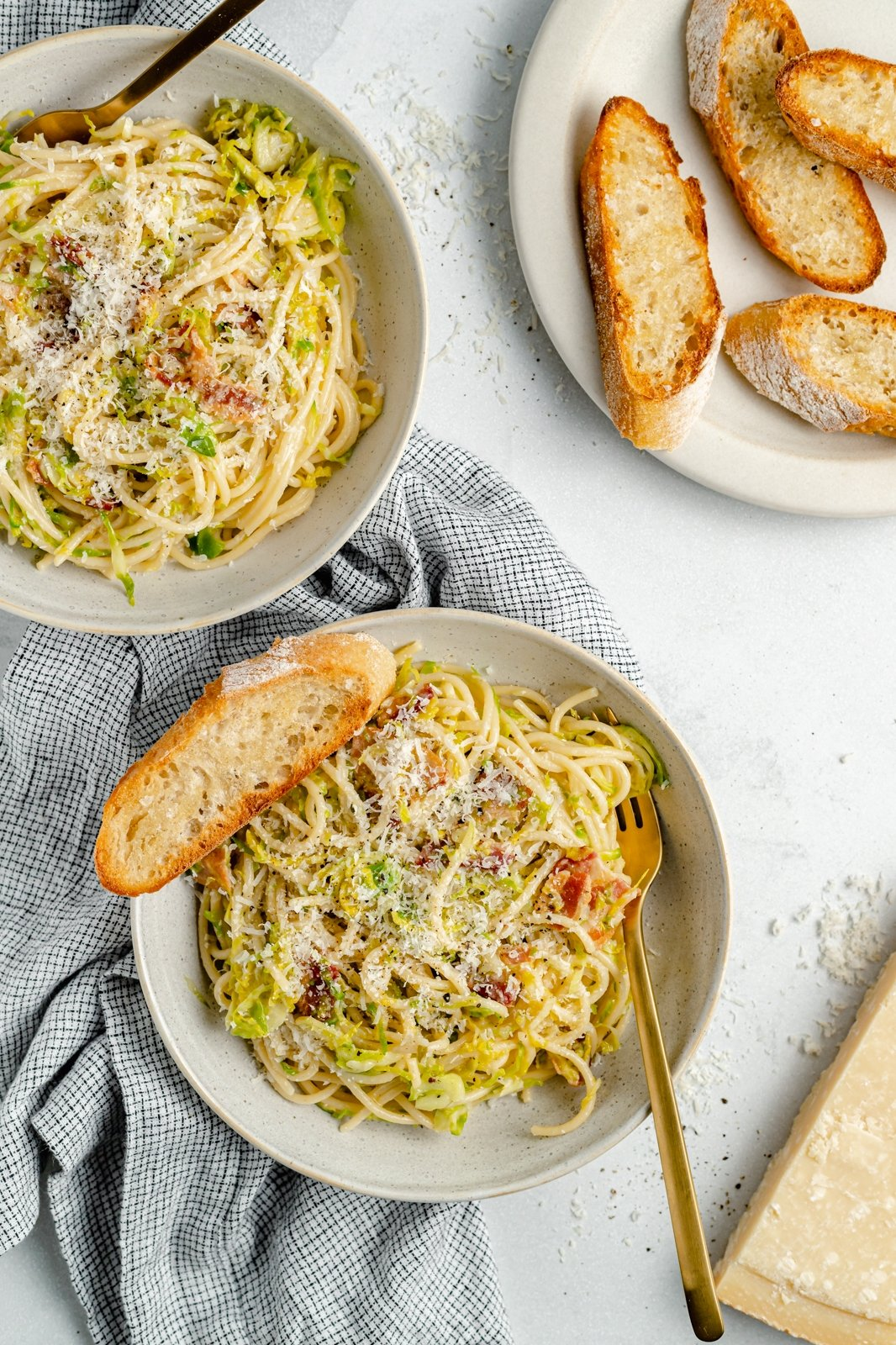 easy brussels sprouts spaghetti with bacon in bowls with garlic bread