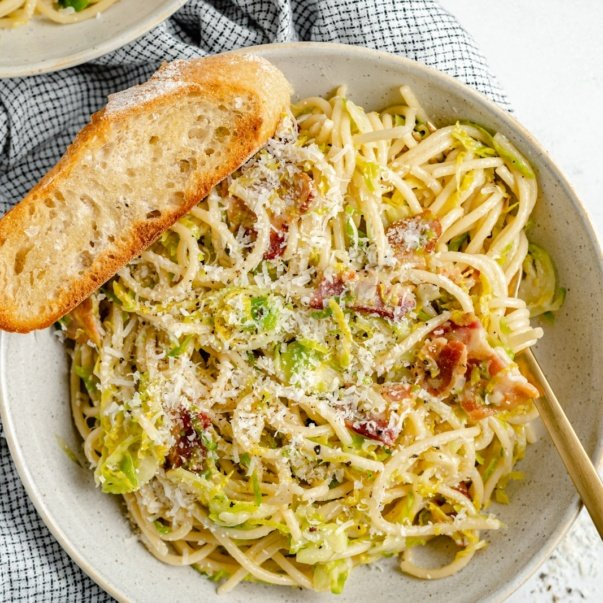 bacon brussels sprouts spaghetti in a bowl with a slice of bread