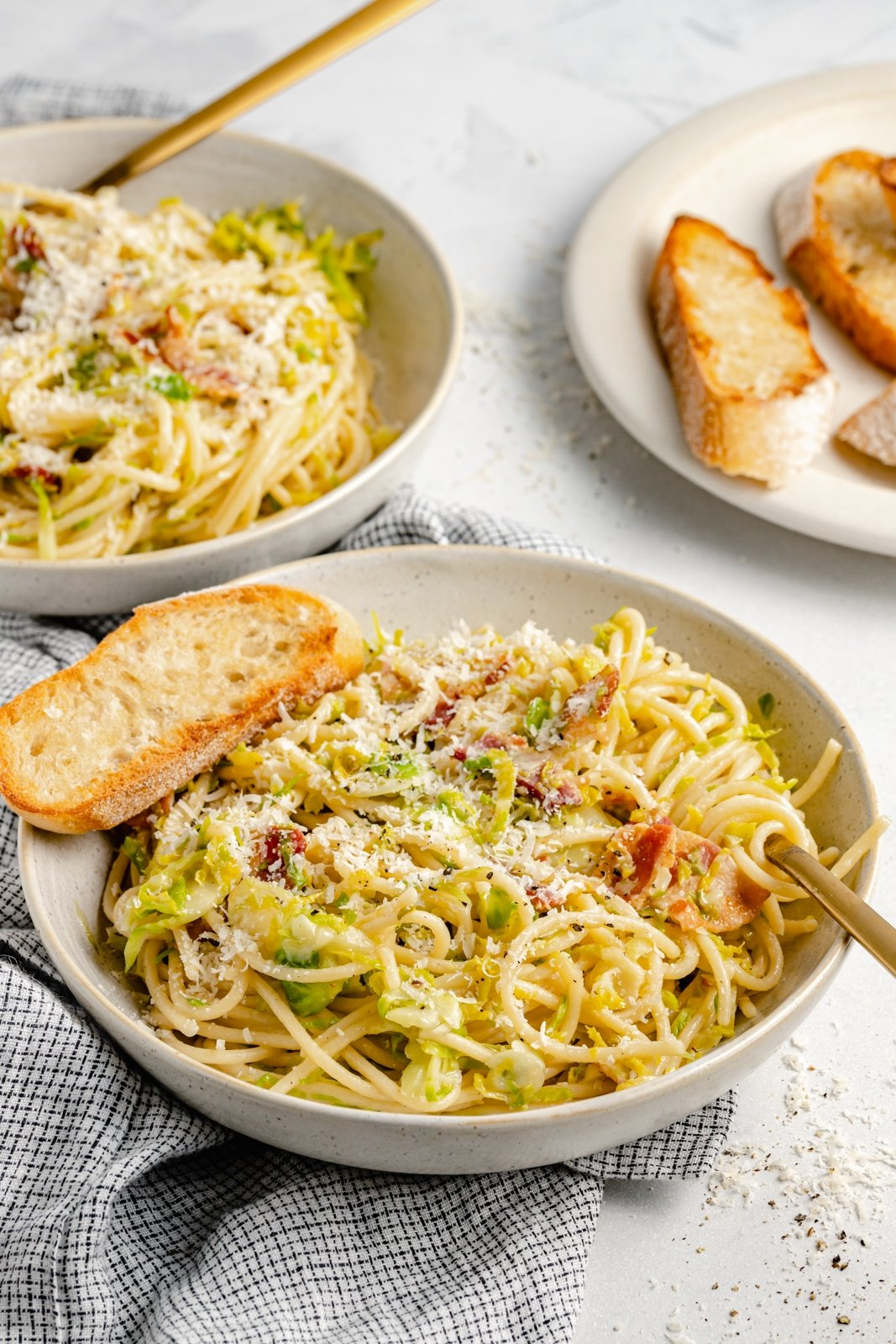 brussels sprouts spaghetti in a bowl with a slice of bread