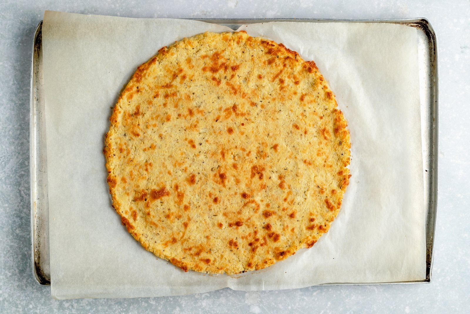 baked cauliflower pizza crust on a baking sheet