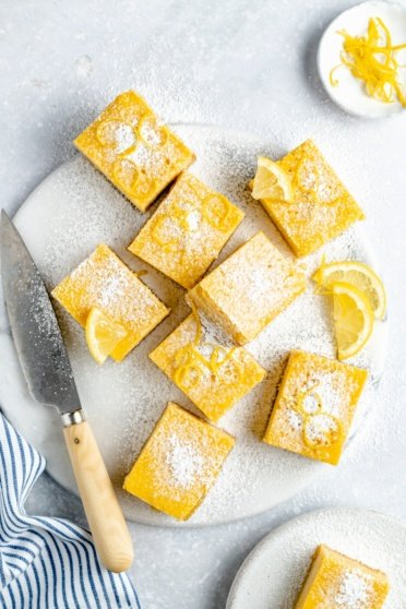 healthy lemon bars on a serving tray with a knife