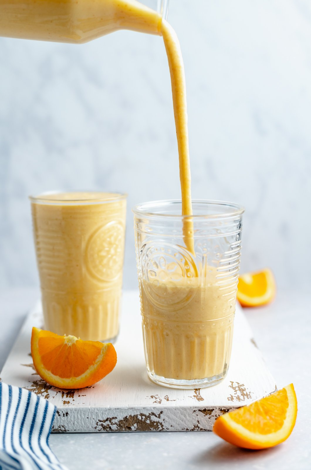 pouring an orange smoothie into glasses