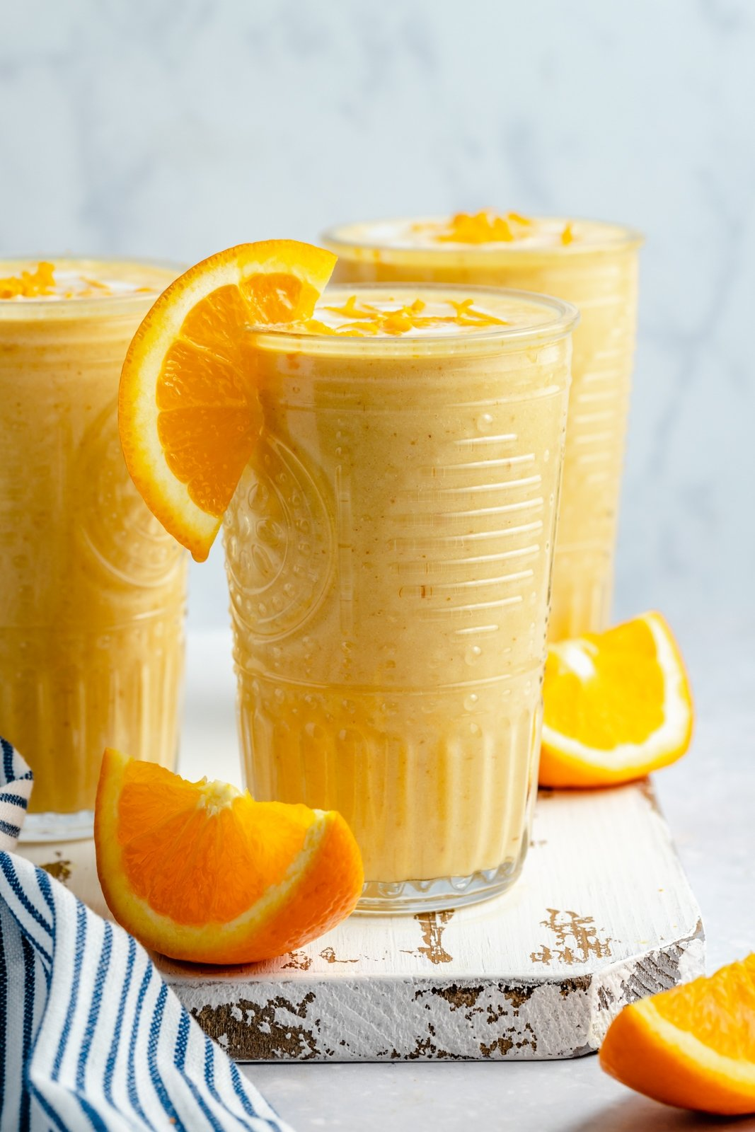 healthy orange smoothie in a glass with an orange wedge