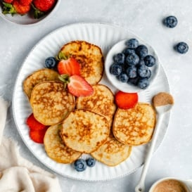 baby banana pancakes on a plate with berries