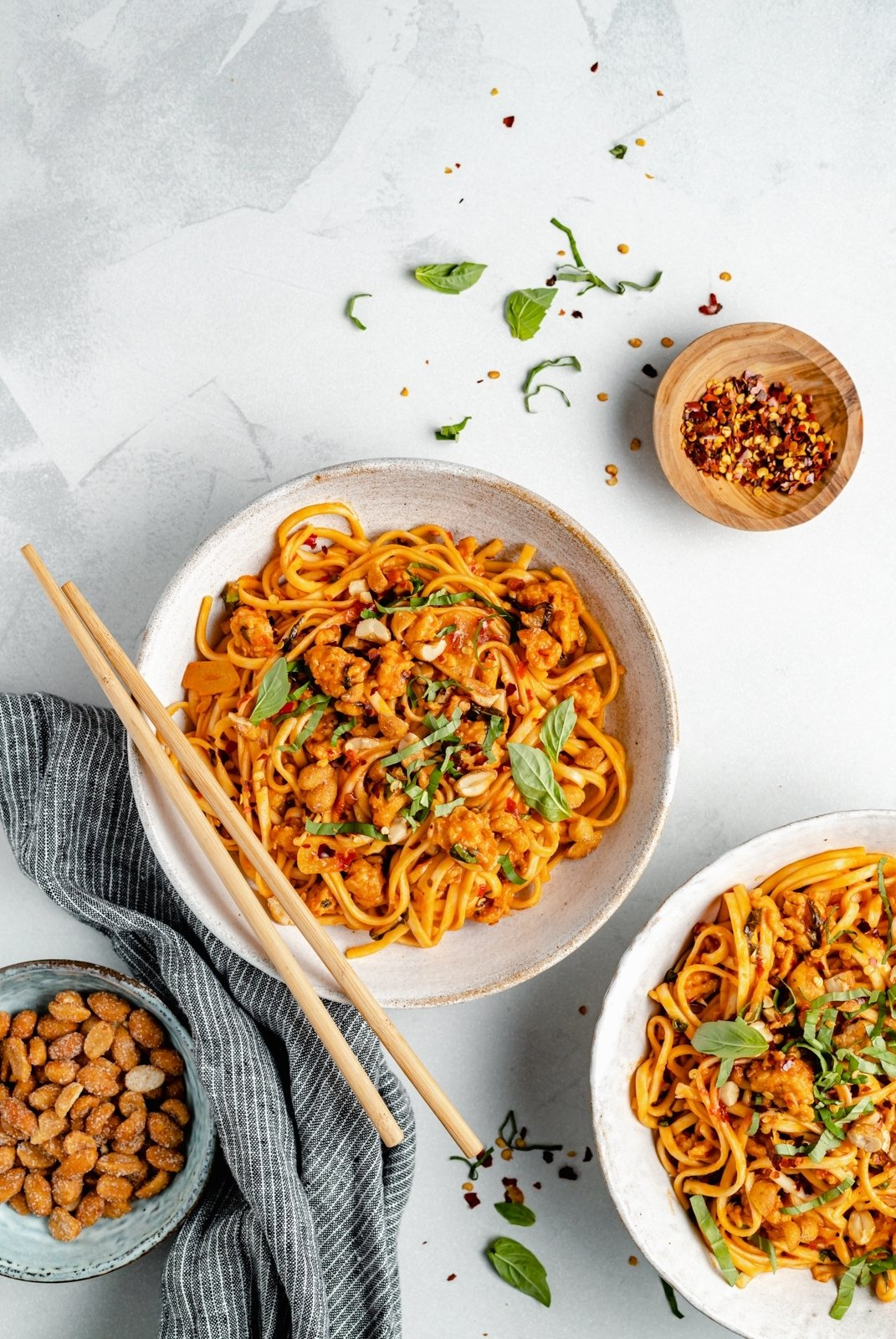 hot chili chicken noodles in bowls with chopsticks
